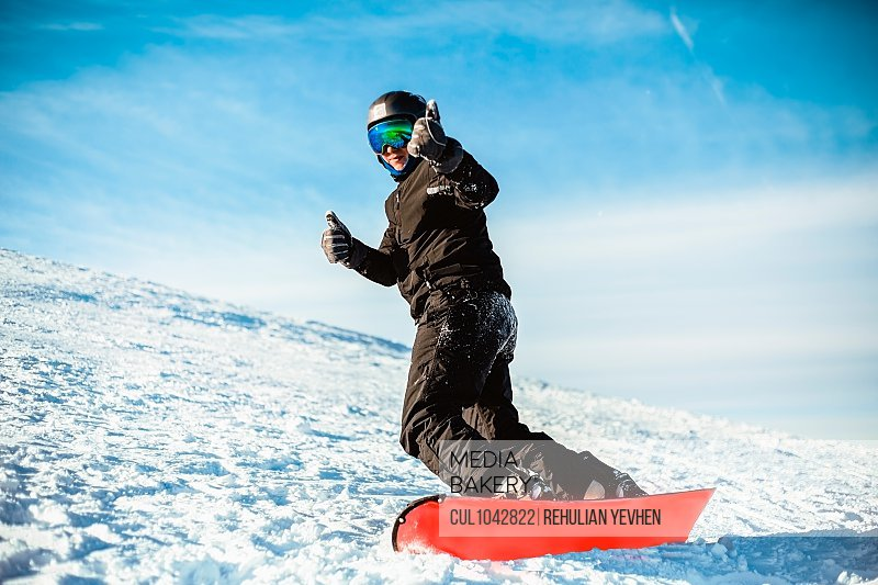 A person wearing a black ski suit, helmet and goggles skiing down a mountain on a red snowboard.