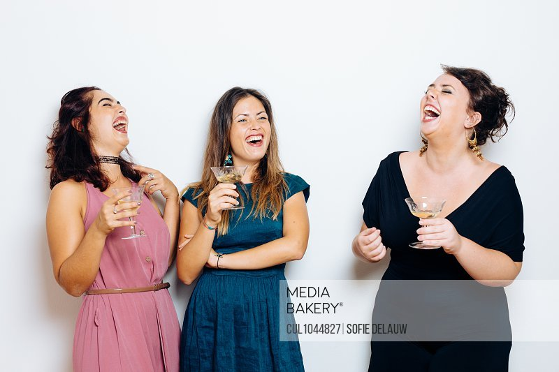 Friends laughing and celebrating with drinks