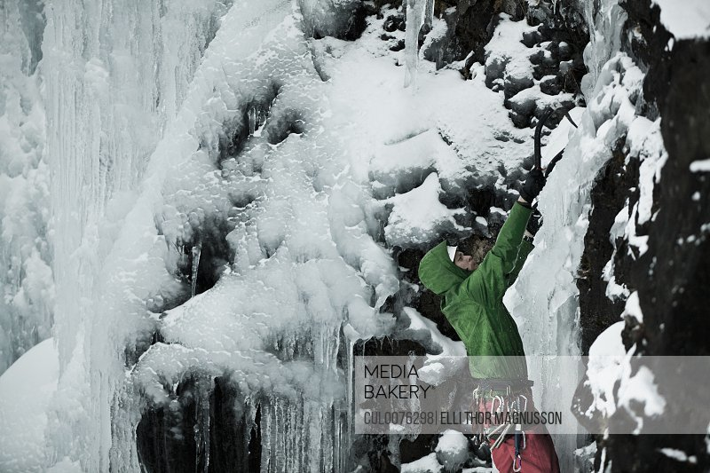 Climber with picks descending snowy hill