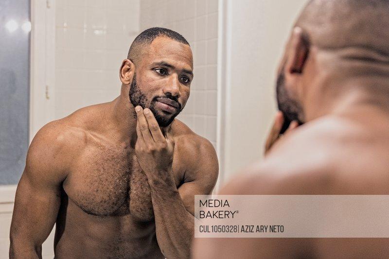 Man looking in the mirror, touching beard