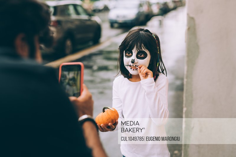 Father photographing daughter at Halloween