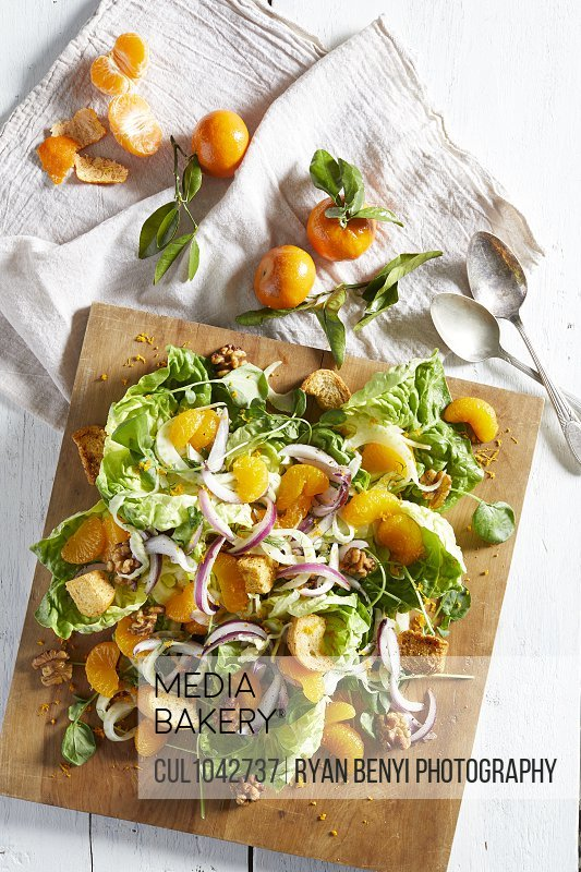 Overhead view of  a wooden board with a salad with red onions, croutons, orange segments and nuts.