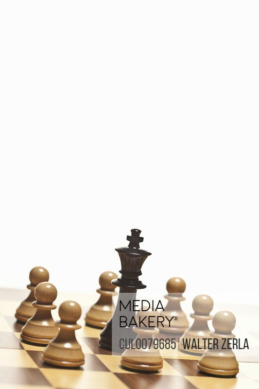 White pawns surrounding black chess king