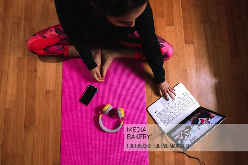 Young woman sitting on yoga mat, having video call on laptop