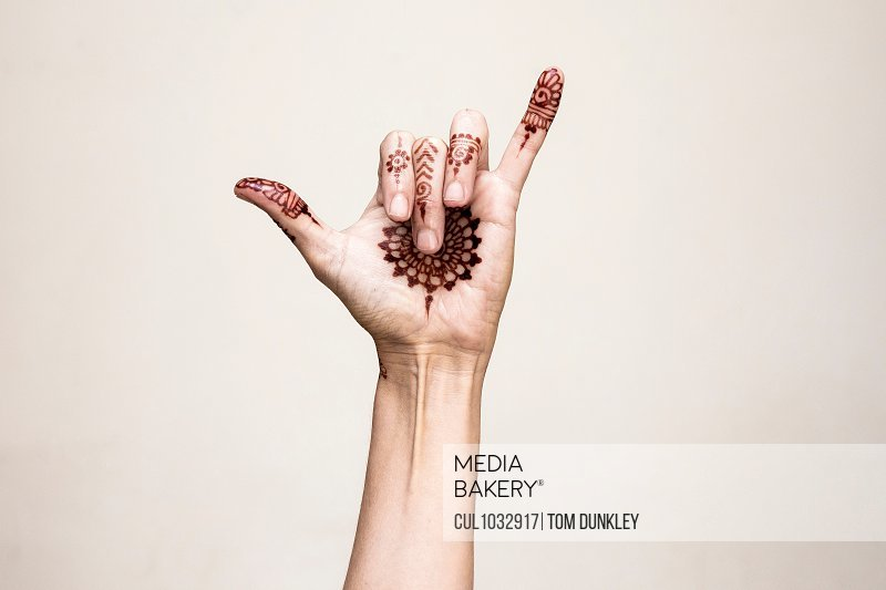 Hand with henna tattoo making gesture