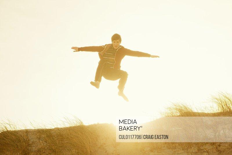 Boy jumping for joy on beach/n