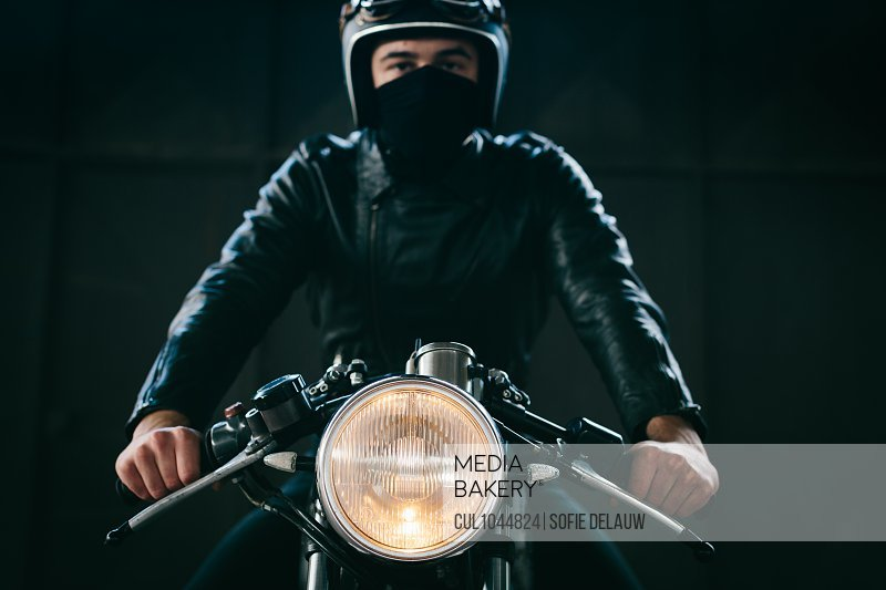 Young male motorcyclist on vintage motorcycle in garage, portrait