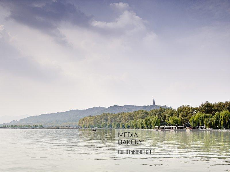 Distant view of tourists on lakeside West Lake Hangzhou Zhejiang China