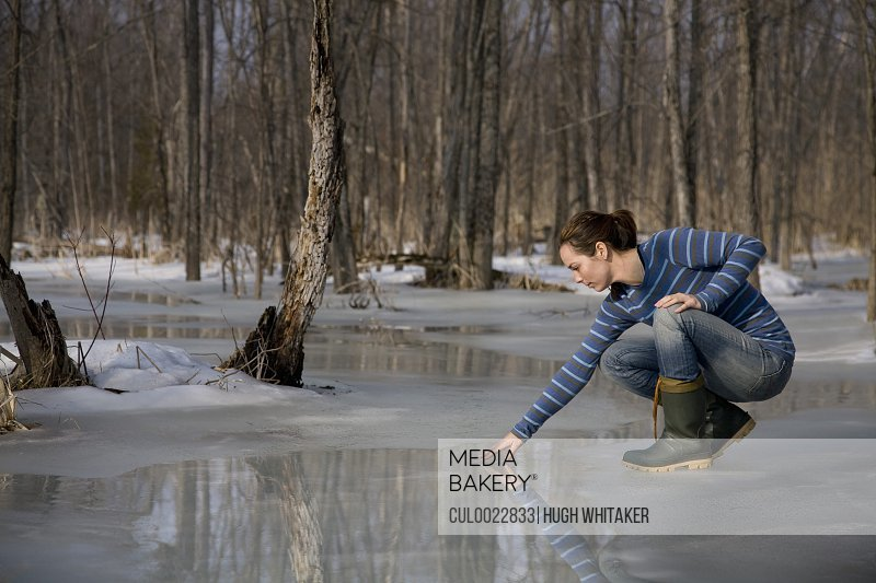 Woman Testing Melting Ice on Pond
