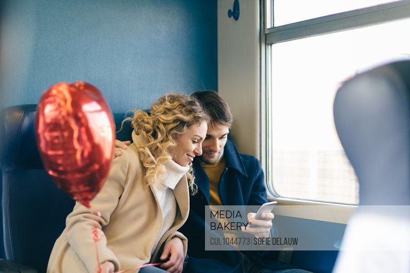 Couple with heart shaped balloon using smartphone inside train