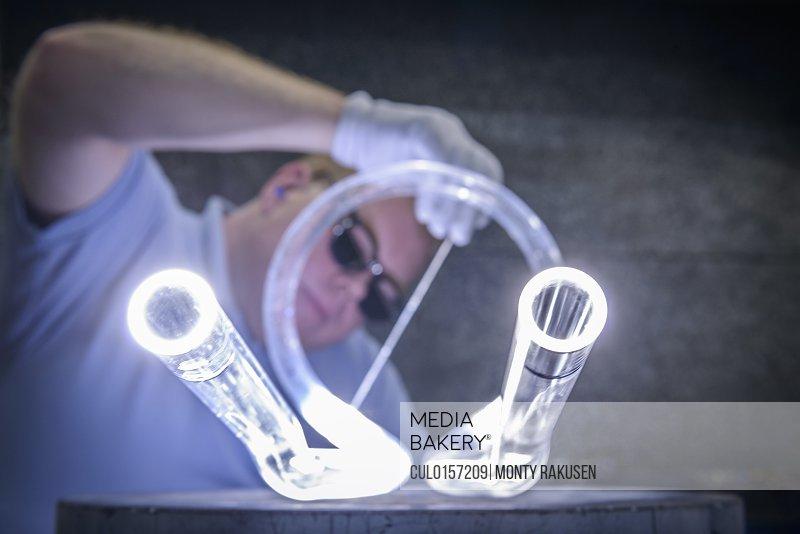 Industrial glass blower welding glass tubes