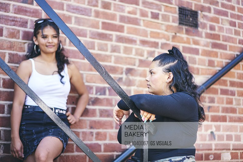 Young woman and her teenage sister on fire escape