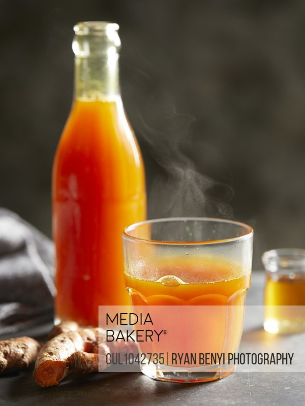 A bottle and drinking glass of bright orange winter tea beside a turmeric root.