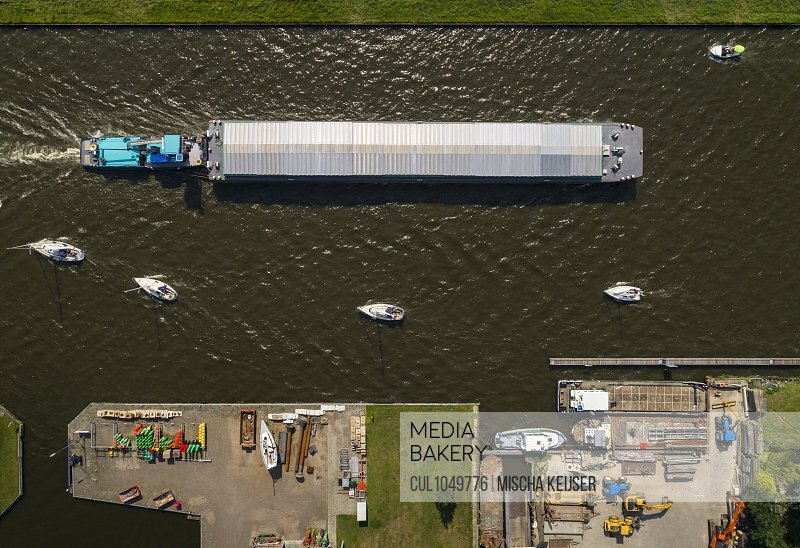 Pleasure boats and inland shipping pass each other, Uitwellingerga, Friesland, The Netherlands