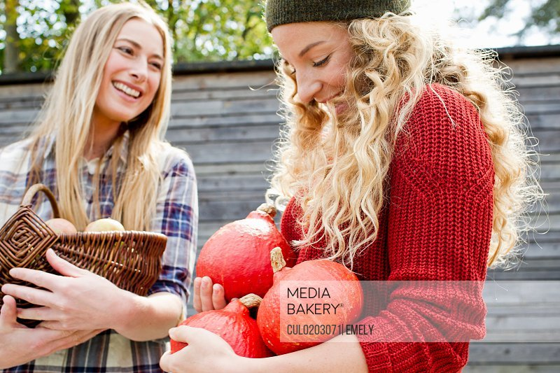 Two women holding homegrown produce