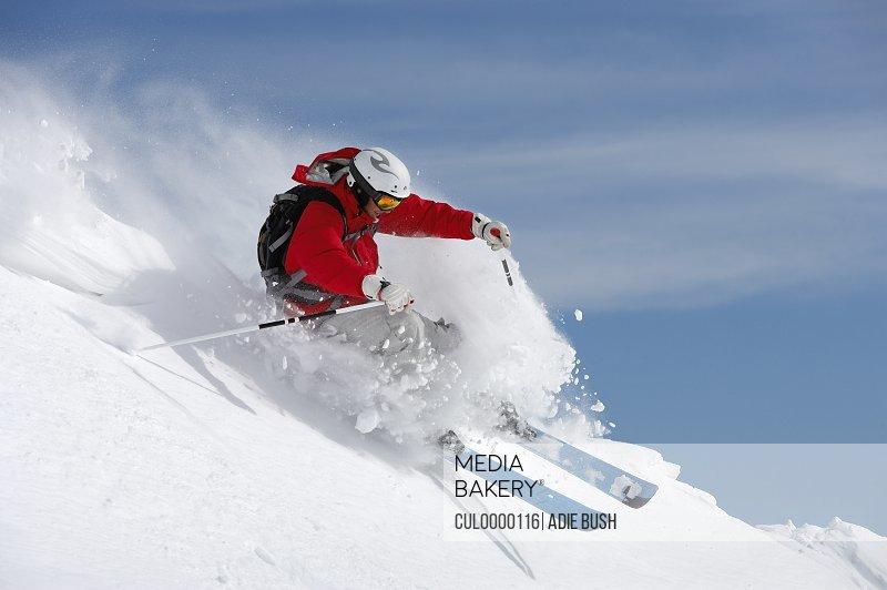 man skiing on slope sending up snow spray