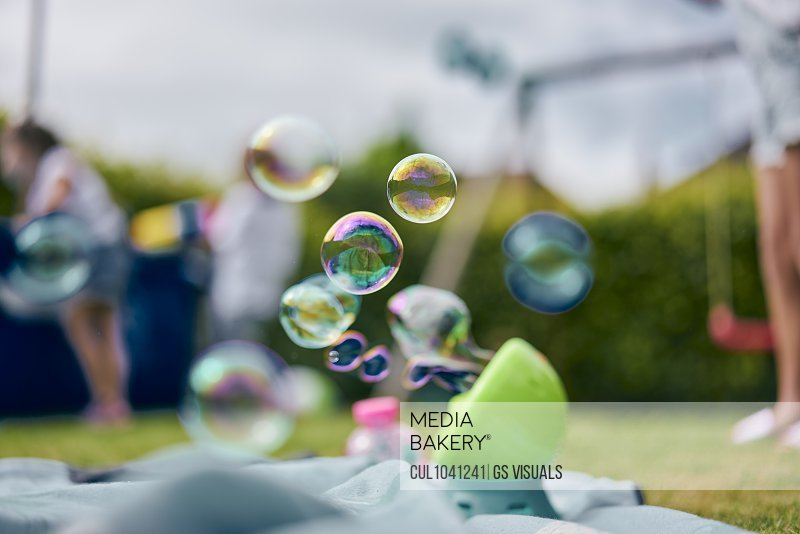 Soap bubble machine, family playing in garden in background