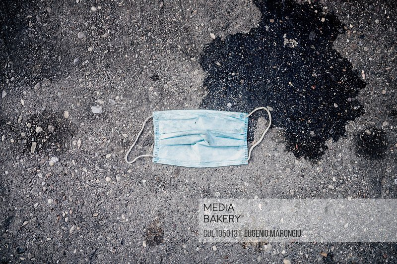 Discarded disposable face mask on sidewalk during 2020 Covid-19 Lockdown, Milan, Italy