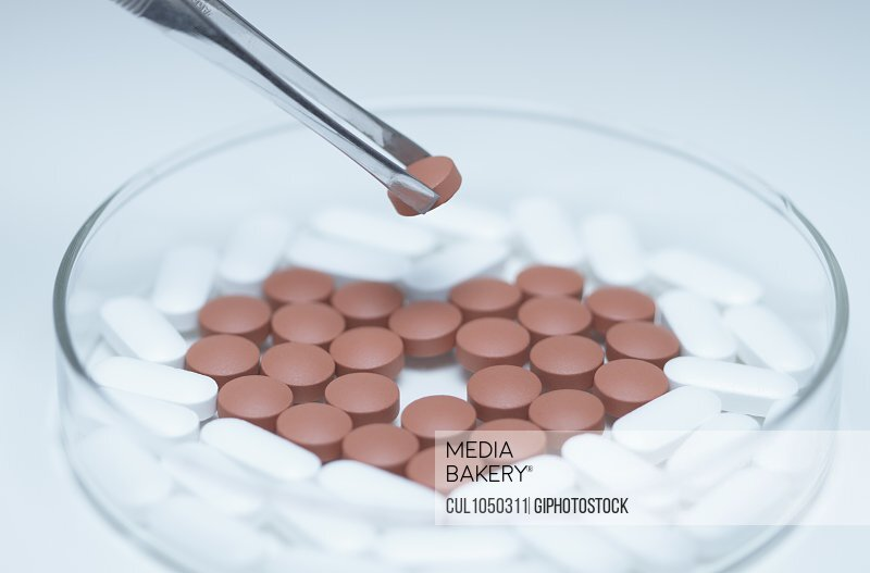 Tweezers holding a pill over a Petri dish with generic pills forming heart symbol