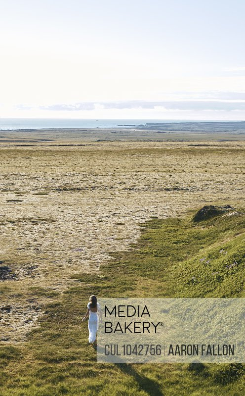 A woman wearing a long white dress walking away from the camera along a strip of grass towards the sand beach and sea.