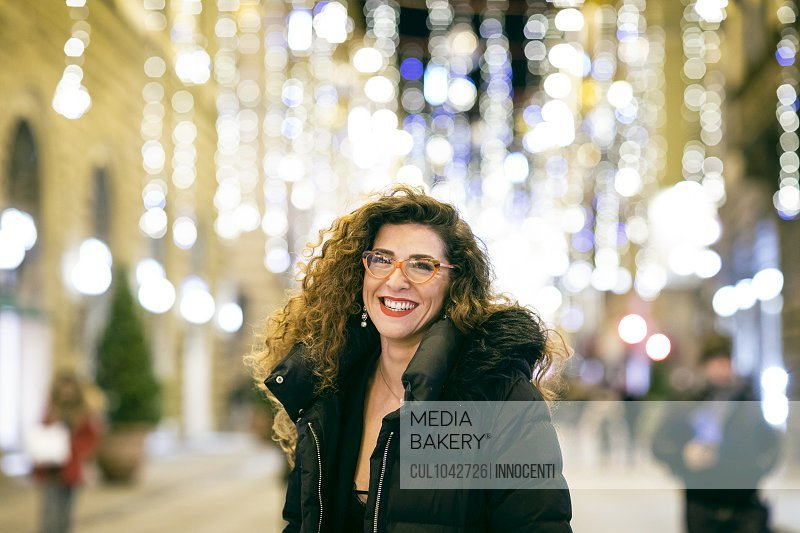A woman dressed to go out for the evening, smiling on a street in Florence.