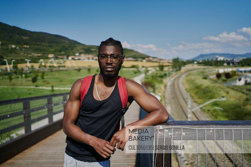 Young man on bridge, looking at camera