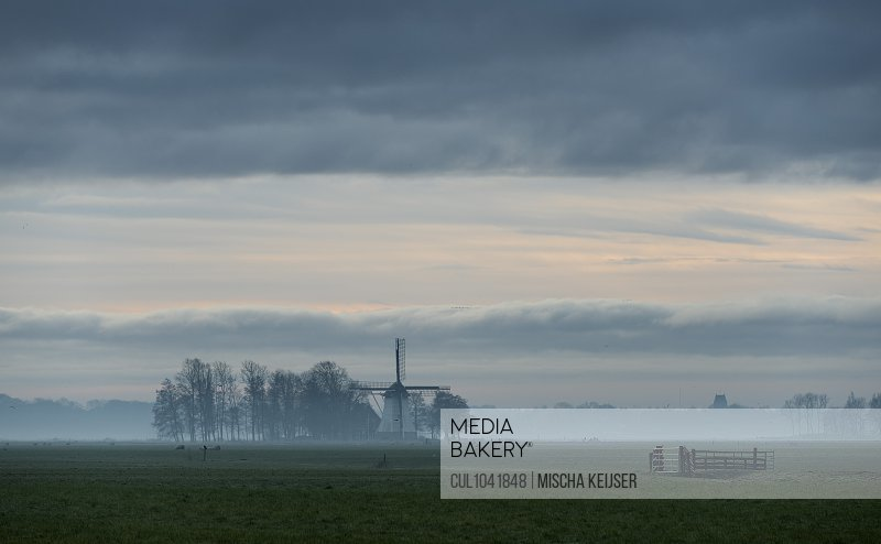 Early morning fog over historic windmill in old polder, Wyns, Friesland, Netherlands