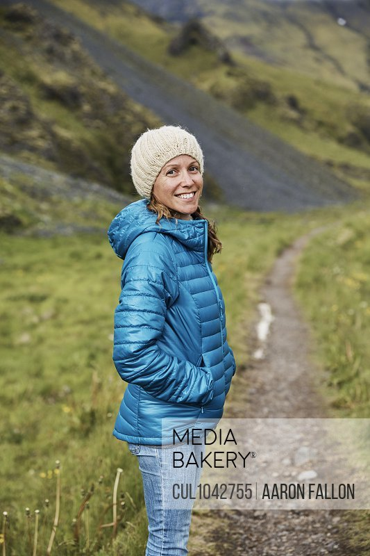 A woman wearing a blue jacket and white knitted hat smiling at the camera standing on a path in a green steep sided valley.