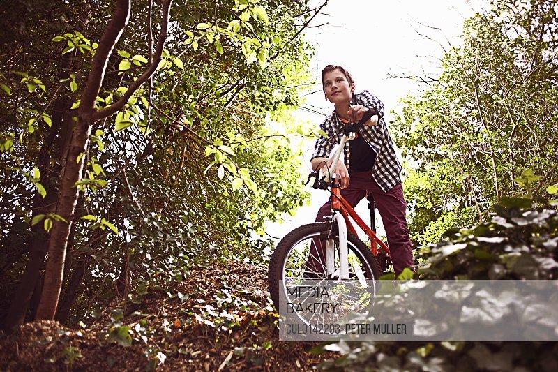 Boy cycling through forest