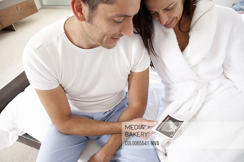 Couple examining sonogram together