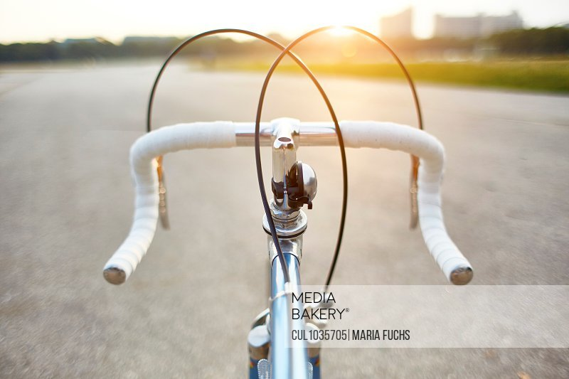Racing bike on rural road, personal perspective view of handlebars