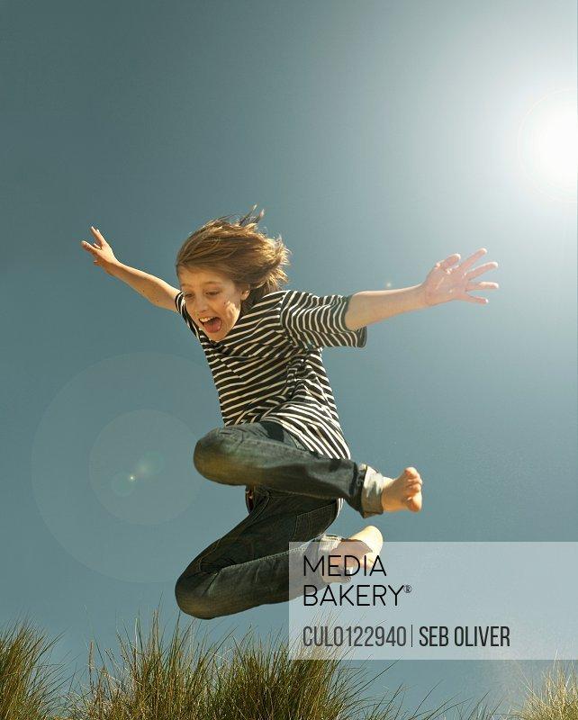 Teenage boy jumping against clear blue sky/n