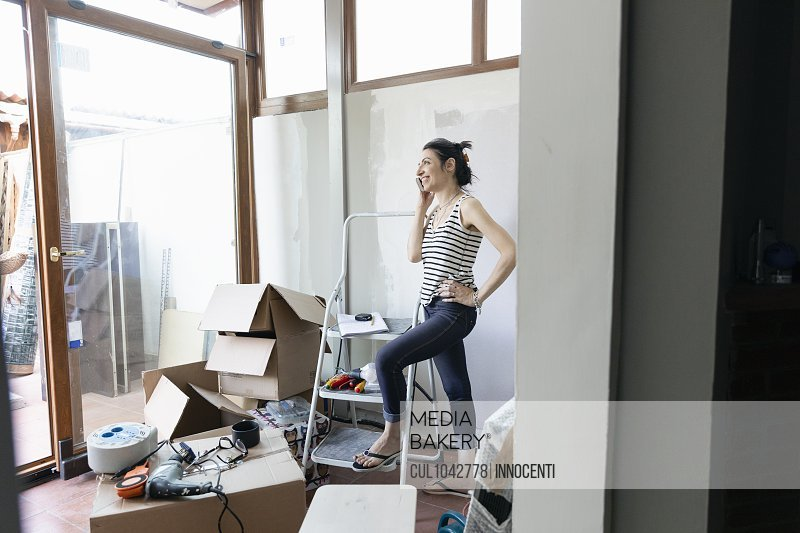Woman standing with one foot on the bottom of a stepladder talking on a phone with cardboard boxes nearby.