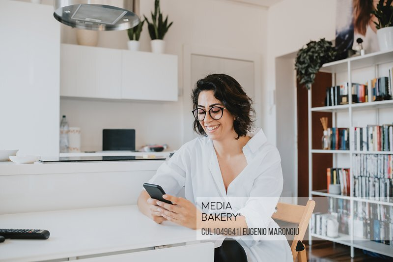 Woman with brown hair wearing glasses sitting at table in an apartment, using mobile phone.