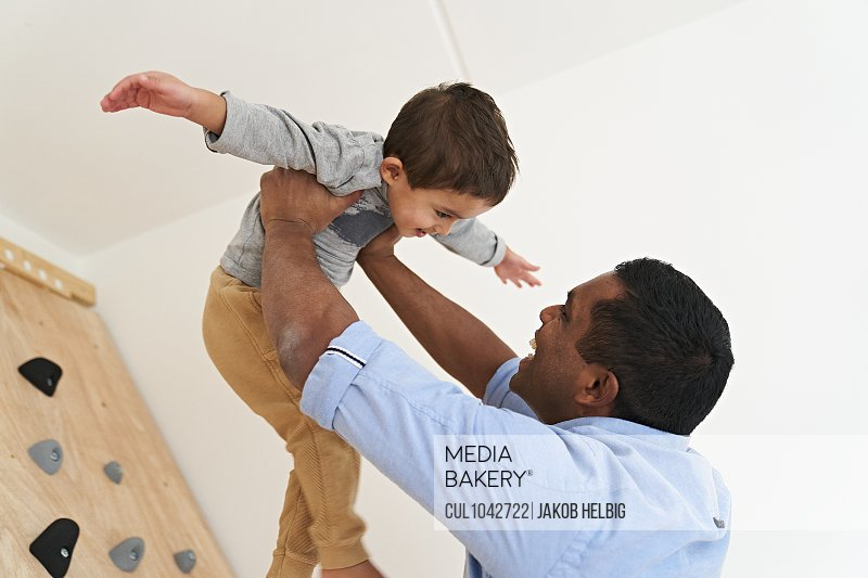 A father holding his son above his head, both smiling, the son with arms stretched out wide.