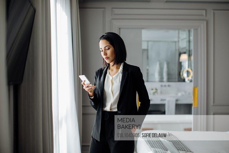 Businesswoman using smartphone in suite