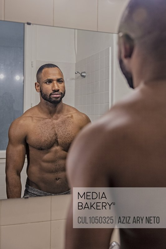 Bare chested man looking at himself in bathroom mirror