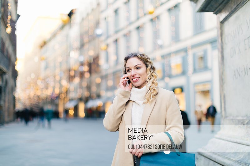 Woman using smartphone at piazza, Firenze, Toscana, Italy