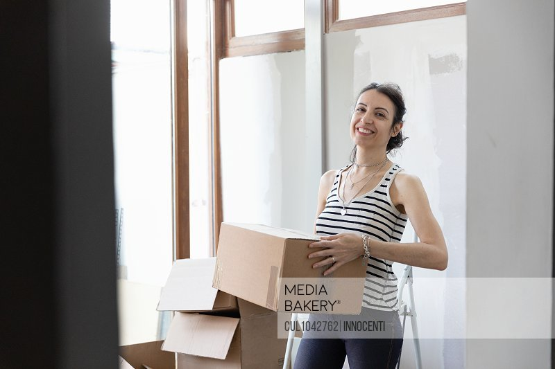A woman smiling and carrying a cardboard box.