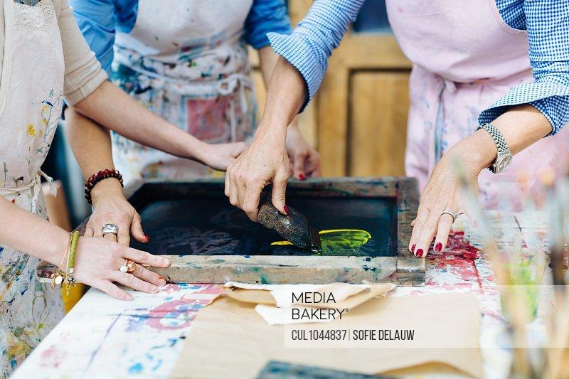 Three women working on silk screen print in creative studio