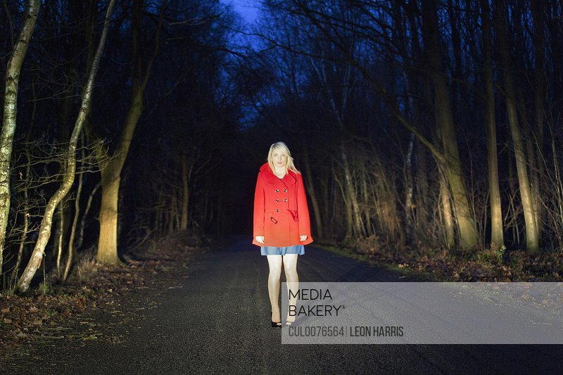 Woman standing on road in woods