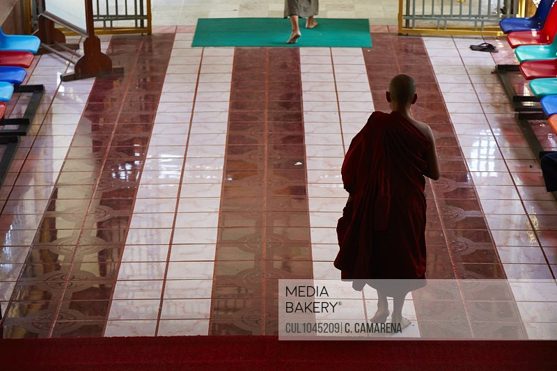 Rear view of silhouetted buddhist monk in temple, Yangon, Myanmar