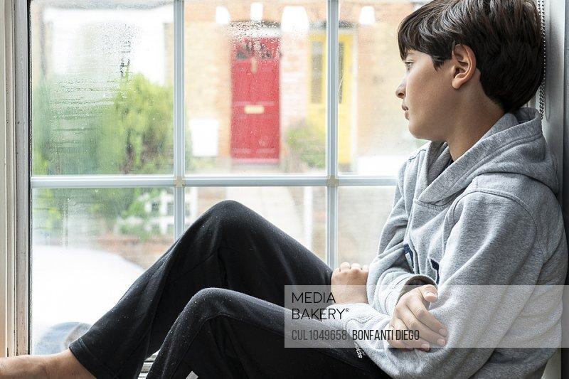 Boy sitting in his bedroom, looking through window during Coronavirus crises.