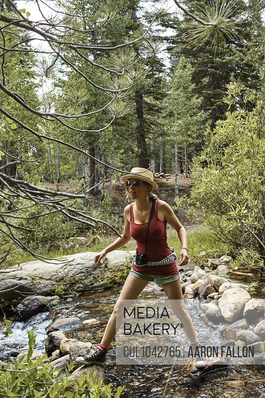 A woman wearing shorts and a tee shirt, sunglasses and a straw hat standing on rocks in a stream in the forest.