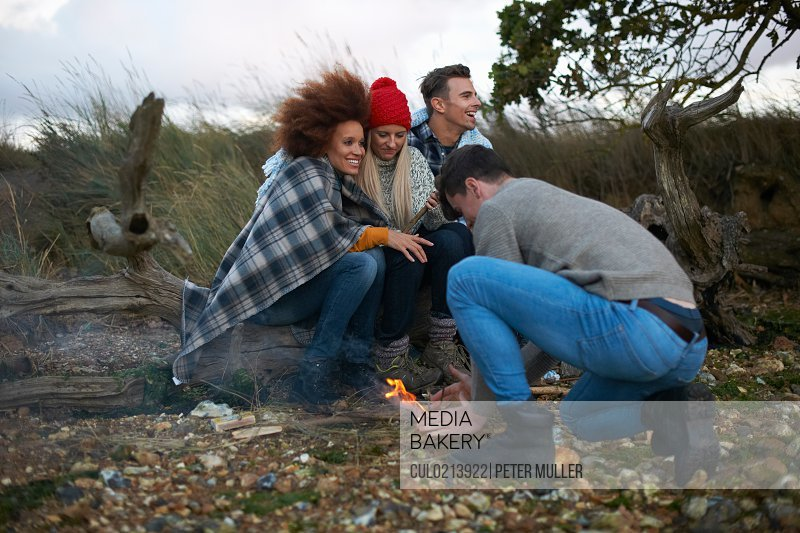Four adult friends igniting campfire on windy beach