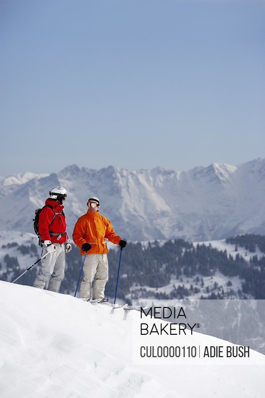two skiers standing on slope talking to each other