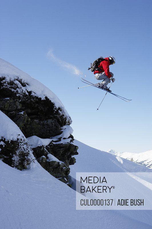 male skier jumping over rock on snow covered slope