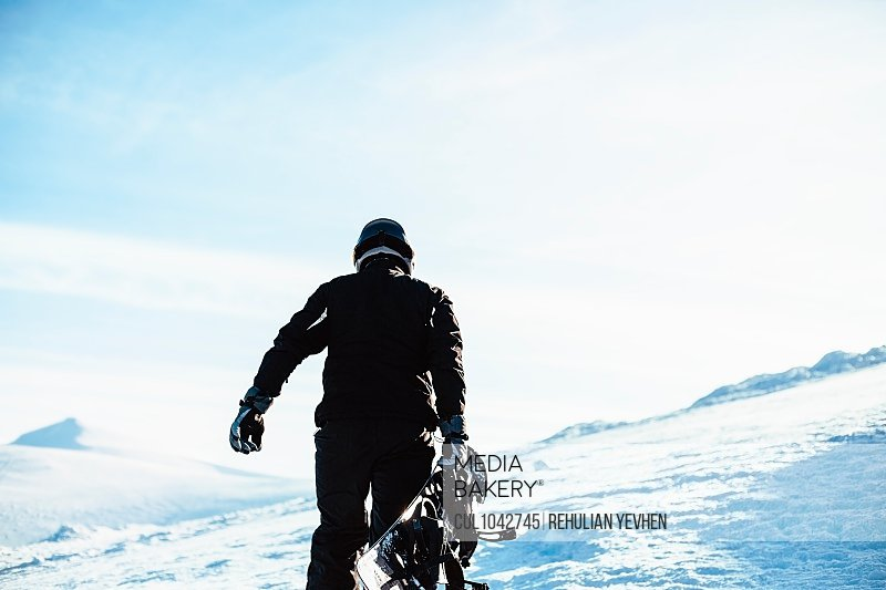 A person wearing a black ski suit and helmet holding a snowboard standing on top of a snowy mountain.