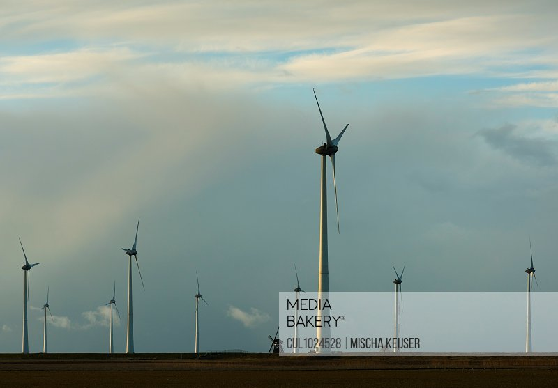 Modern wind turbines around lone traditional windmill, Delfzijl, Groningen, Netherlands