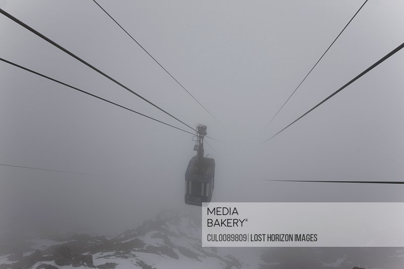 Ski lift on wires in fog